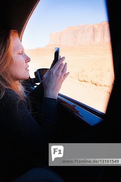 Frau fotografiert mit einem Smartphone aus dem Autofenster  Monument Valley  Utah  USA