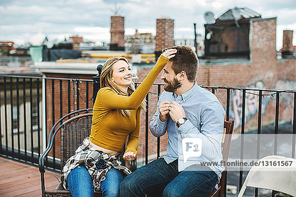Happy young couple sitting on city rooftop terrace
