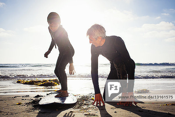 Father and son practicing with surfboard on beach  Encinitas  California  USA