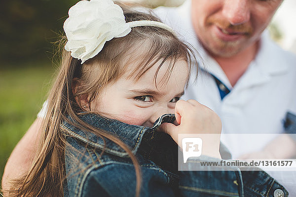 Young girl sitting with her father  hiding face with jacket