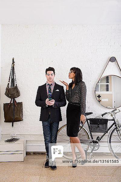 Junges Paar  Mann benutzt Smartphone und Frau bläst einen Kuss