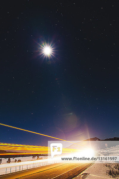 Straßenbeleuchtungspfade und Vollmond bei Nacht  Pagosa Springs  Colorado  USA