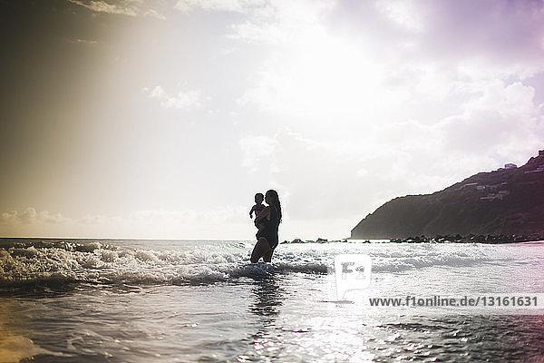 Mutter hält Tochter  paddelt im Meer