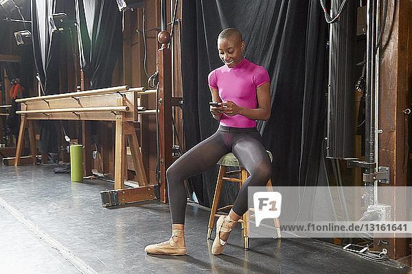 Balletttänzer auf Hocker sitzend beim Schreiben von Texten