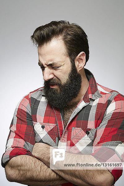 Studioporträt eines gequälten bärtigen jungen Mannes mit verschränkten Armen