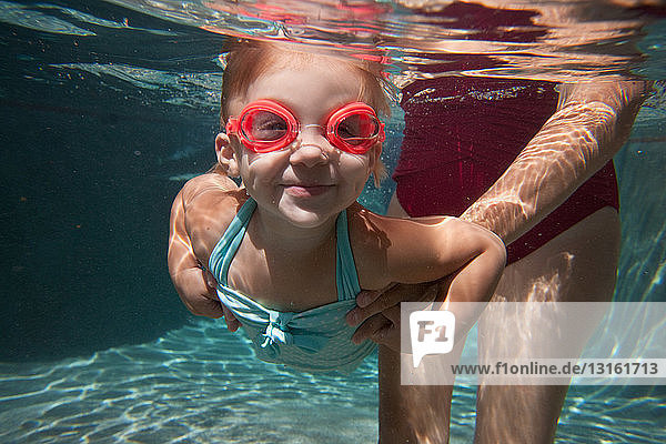 Underwater portrait of girl learning to swim