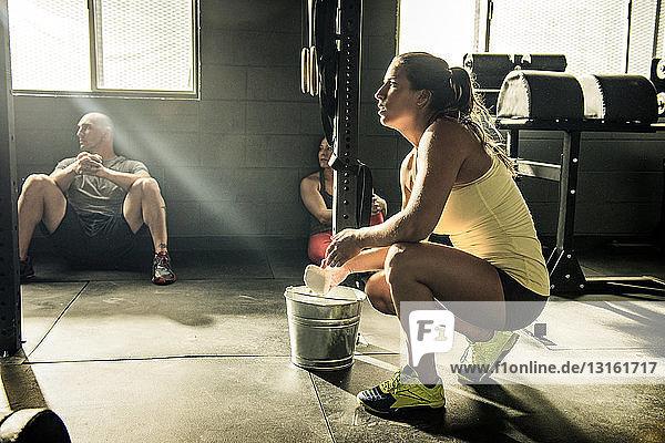 Junge Frau bereitet in Turnhalle Hände mit Kreide vor