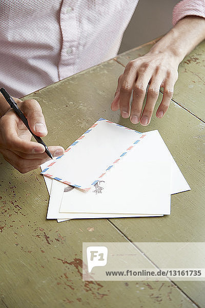 High angle view of young mans hands writing air mail letter