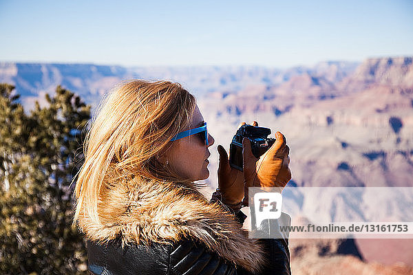 Woman photographing Grand Canyon  Arizona  USA