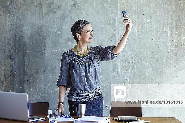 Reife Geschäftsfrau beim Selbstporträt im Amt