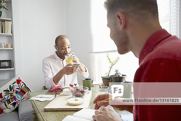 Man sitting at dining table drinking orange juice looking at smartphone