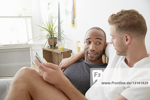 Homosexual couple lying in bed face to face holding smartphone