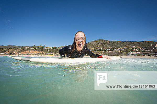 Front view of young woman lying on surfboard looking at camera sticking out tongue. Los Angeles  California  USA