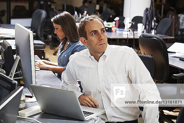 Mittelgroßer erwachsener Mann mit Laptop im Büro
