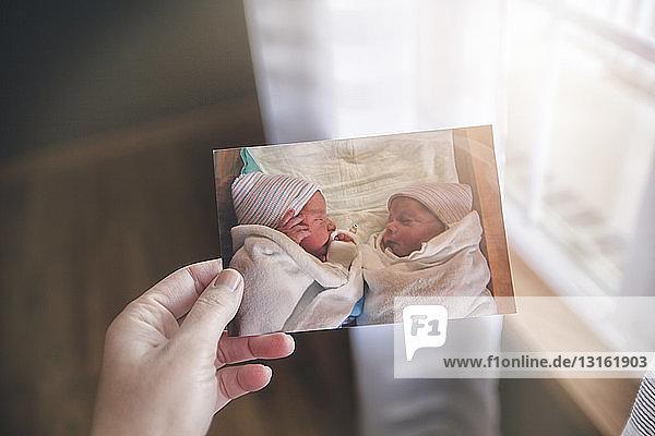 Hand der Mutter mit dem Foto der Zwillinge