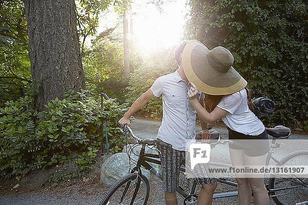 Junges Paar mit Tandemfahrradkuss auf der Landstraße
