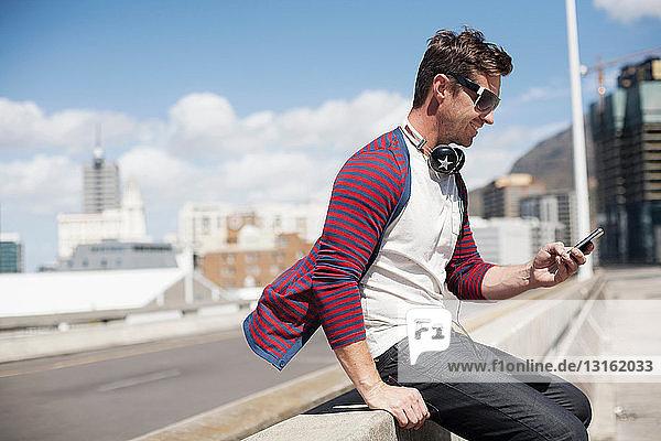 Mann benutzt Mobiltelefon auf der Straße in der Stadt