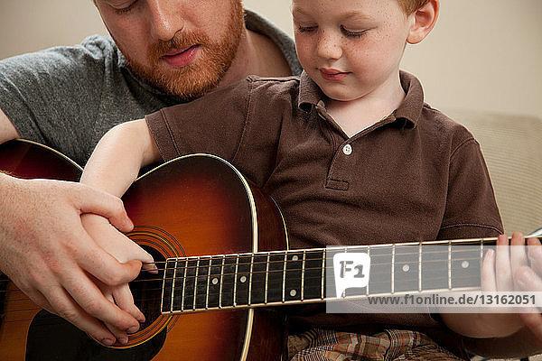 Vater lehrt Sohn Gitarre spielen