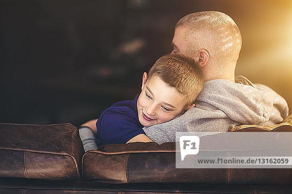 Reifer Mann entspannt sich auf Sofa und umarmt Sohn