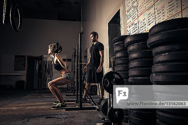 Female weight-lifter being watched by trainer