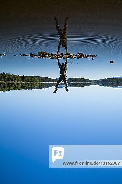Mann macht Handstand am McCulloch Lake entlang des KVR-Pfades  Okanagan Highlands  Britisch-Kolumbien  Kanada
