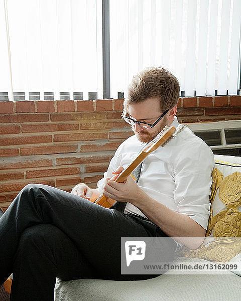 Junger Mann übt auf der E-Gitarre