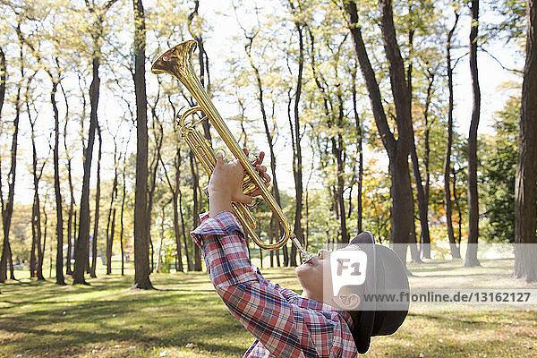 Trilby tragender Junge spielt Trompete in Wäldern