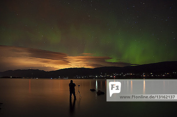 Photographer in Okanagan Lake photographing aurora borealis  Kickininee Provincial Park  Penticton  British Columbia  Canada