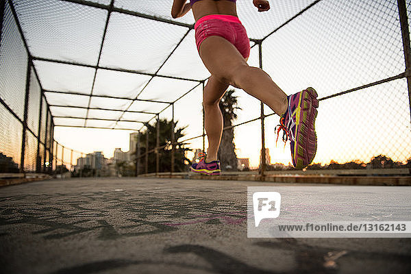 Legs of female jogger running on walkway