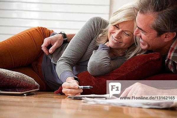 Paar macht Kreuzworträtsel auf dem Boden