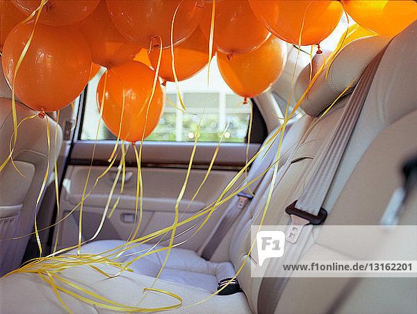 Orangefarbene Luftballons auf dem Rücksitz eines Autos