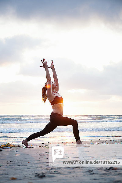 Mid adult woman practicing warrior yoga pose on beach at sunset