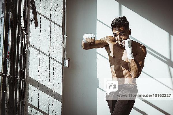 Frontansicht eines jungen Mannes in Turnhalle in Boxhaltung mit Blick weg