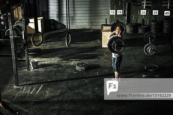 Junger Mann trainiert mit Langhantel in Turnhalle