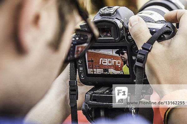 Nahaufnahme eines Fotografen,  der das Foto eines Mountainbikers vor der Kamera überprüft