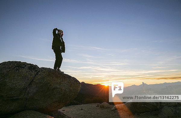Junger Mann schaut bei Sonnenuntergang auf die Landschaft hinaus,  Los Angeles,  Kalifornien,  USA