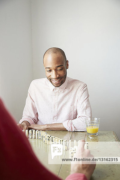 Men placing dominos on edge smiling