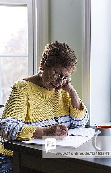 Ältere Frau schreibt am Schreibtisch
