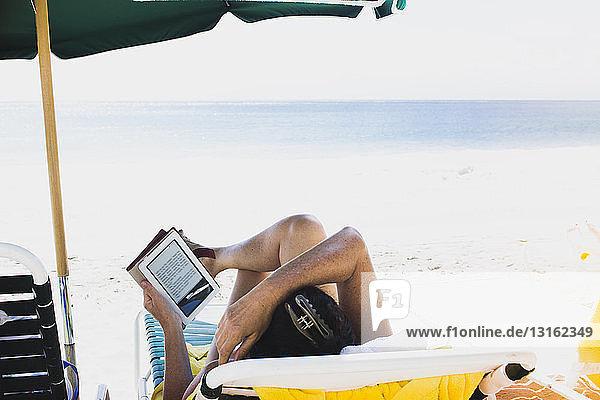Frau liegt auf Sonnenliege und liest E-Book