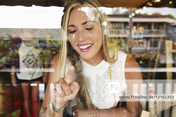 Junge Frau zeigt auf Fenster eines Cafés