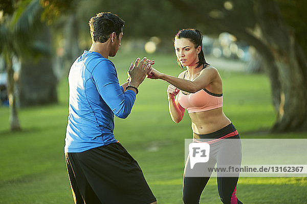 Man and woman in park boxing