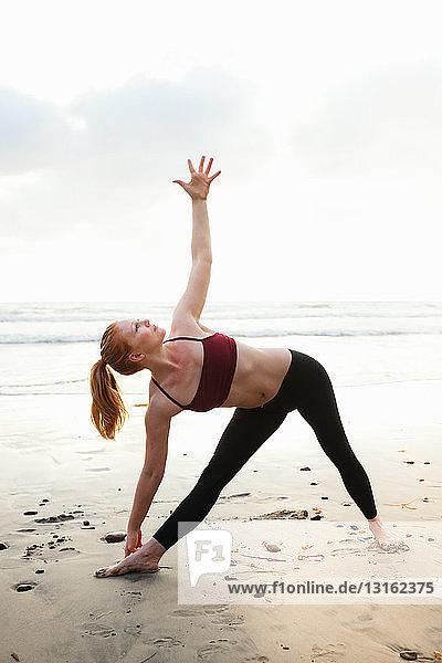 Mittlere erwachsene Frau  die am Strand eine Dreiecks-Yoga-Pose praktiziert
