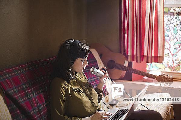Junge Frau mit Kopfhörer und Mikrofon  mit Laptop