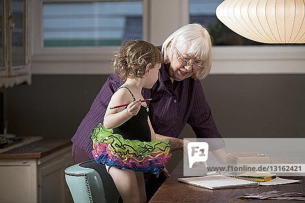 Großmutter und Enkelin stehen am Tisch und zeichnen
