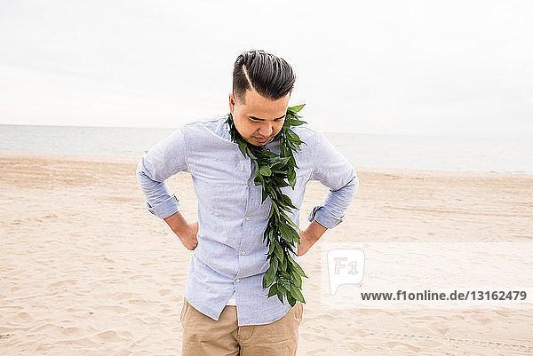 Am Strand stehender Mann mit Laub um den Hals