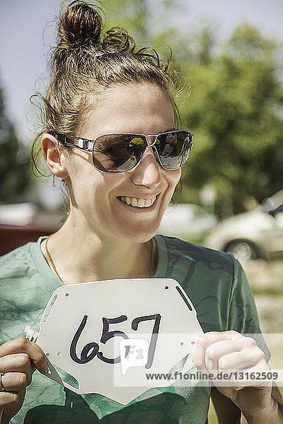 Junge Mountainbikerinnen halten die Startnummer hoch