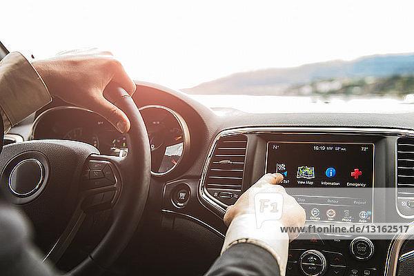 Blick über die Schulter auf die Hand des Mannes über den Touchscreen des Navigationssystems