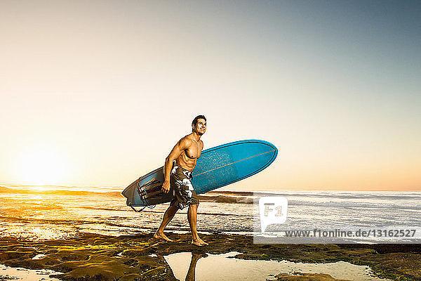 Mann trägt Surfbrett an felsigem Strand