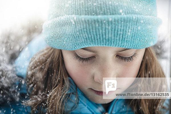 Nahaufnahme eines Mädchens mit Strickmütze  das nach unten schaut und schneit