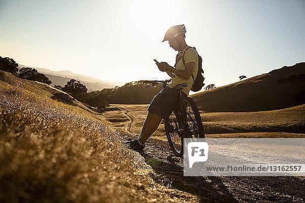 Silhouettierter junger männlicher Mountainbiker mit Smartphone  Mount Diablo  Bay Area  Kalifornien  USA